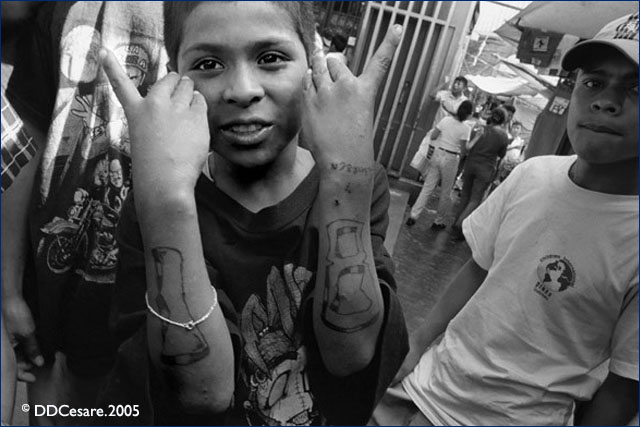 "Young Mara-18 members flashing gang tattoos. Mara-18 is often referred to as the ""Children's Army"" because of the common practice of recruiting young people."